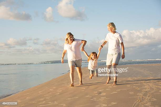 parents swinging daughter in the air - community engagement stock pictures, royalty-free photos & images