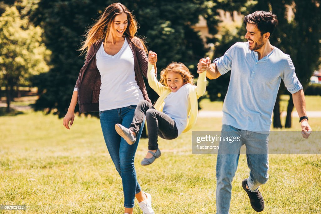 Parents swinging their daughter in the air : Stock Photo