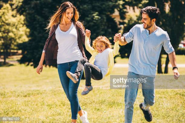 parents swinging their daughter in the air - happy family stock photos and pictures