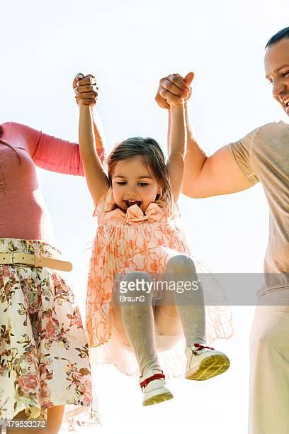 Eltern schwingen ihre kleine Mädchen im Freien und Spaß haben.