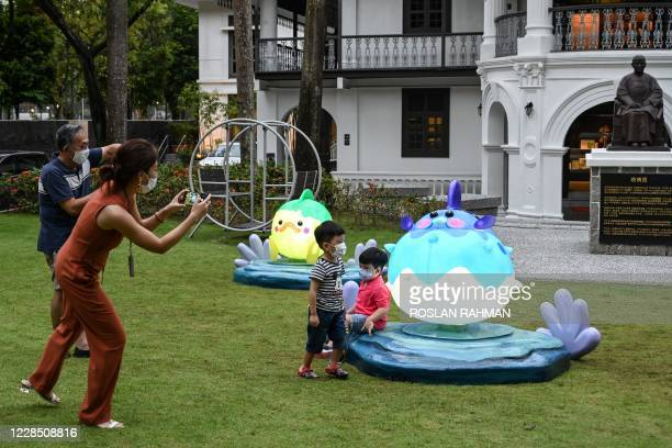 Parents take photographs of their children with fish-shaped lantern installations in the compound of the Sun Yat Sen Nanyang Memorial Hall ahead of...