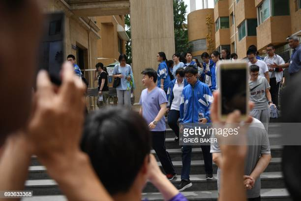 Parents take photos as their children emerge from college entrance exams at a school in Beijing on June 8 2017 Millions of students across China are...
