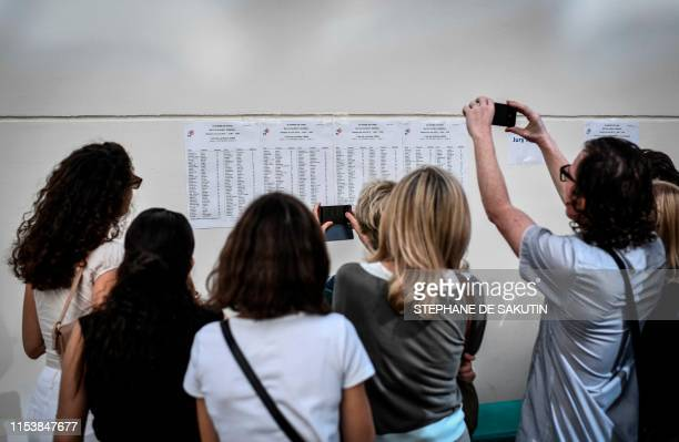 Parents take photos as they check the results of the baccalaureat exam at the Fresnel high school in Paris, on July 5, 2019. - French high school...