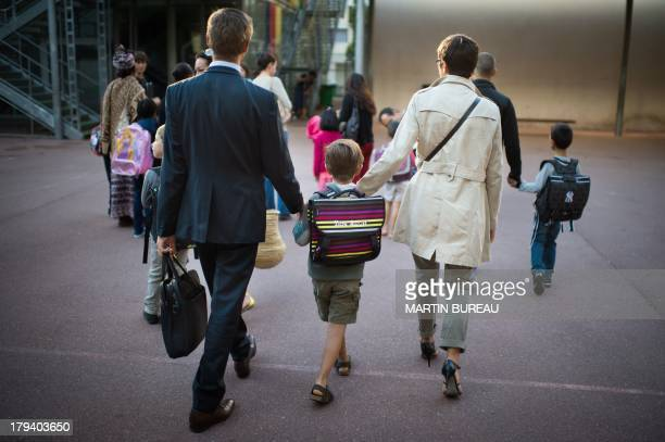 Parents take their child to school on September 3 2013 in Paris on the first day of school More than 12 million pupils went back to school today in...