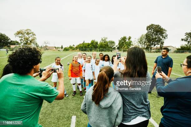 parents taking pictures with smartphones of young female soccer team on field after game - voetbalteam stockfoto's en -beelden