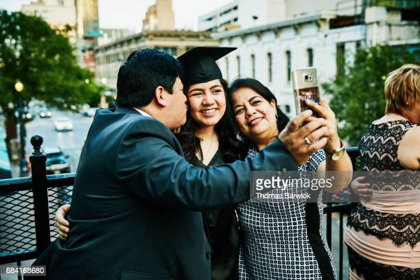 Parents taking selfie on smartphone with graduating daughter during celebration dinner