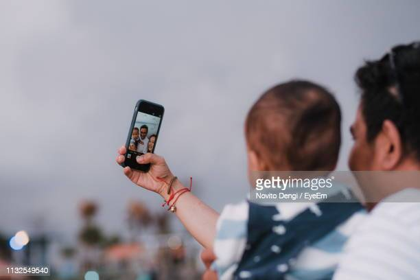 parents taking selfie with toddler son against sky during sunset - photo messaging stock pictures, royalty-free photos & images