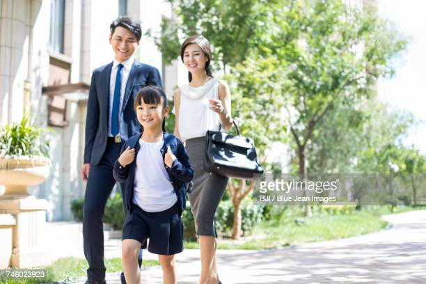 Parents taking their child to school in the morning