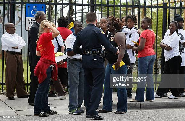 Parents talk to a City of Miami police officer near the front gate at Miami Edison Senior High School after a melee broke out in the campus courtyard...