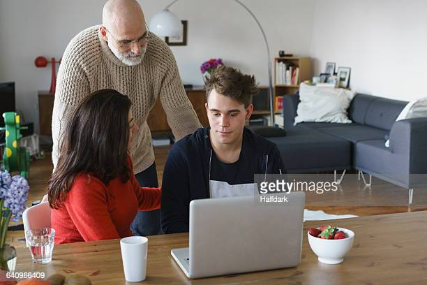 Parents talking with son by table with laptop at home