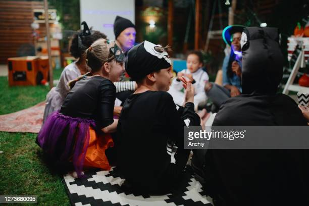 parents telling scary stories to kids at outdoor halloween party - scaredastronaut stock pictures, royalty-free photos & images