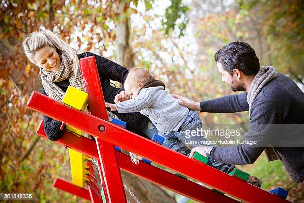 Parents together with son playing on jungle gym, Osijek, Croatia