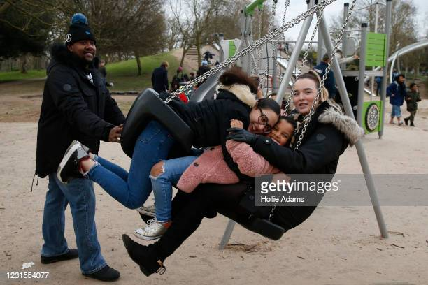 Parents Trevor Daley and Rebecca Nicholson pose for a photo with their daughter Shaniyha Daley and goddaughter Trinity on a swing at Victoria Park...