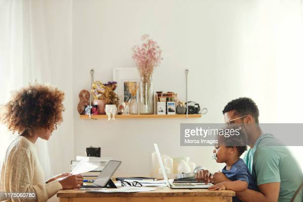 parents using computer while sitting with boy - working from home stock pictures, royalty-free photos & images