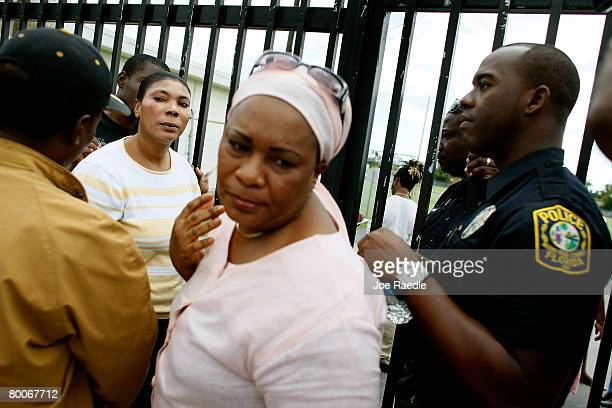 Parents wait as MiamiDade County schools police open a gate to let them in ten at a time to find their children at Miami Edison Senior High School...