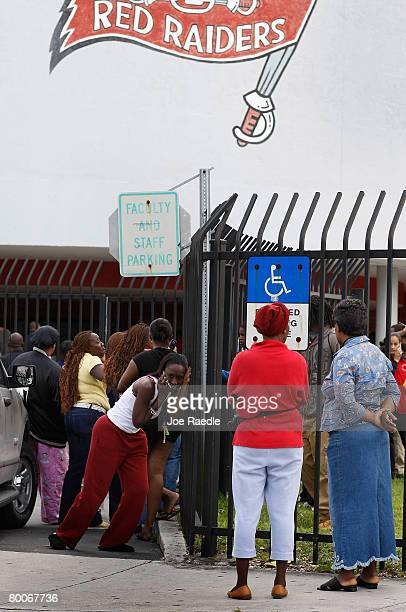 Parents wait near the front gate to Miami Edison Senior High School after a melee broke out in the campus courtyard February 29 2008 in Miami Florida...