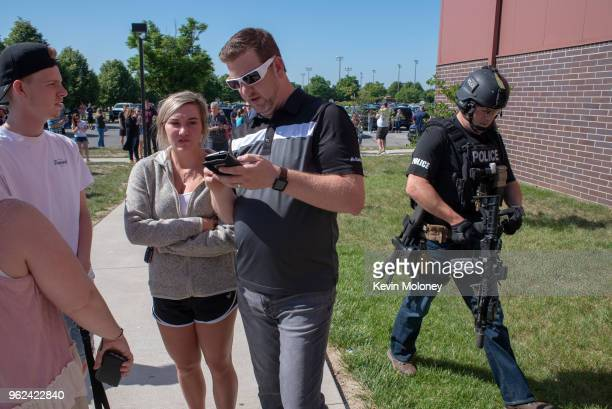 Parents wait while a SWAT officer passes outside Noblesville High School after a shooting at Noblesville West Middle School on May 25 2018 in...