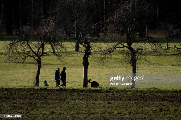 Parents walk with their kid and a dog on March 30, 2020 in Diehsa, Germany.