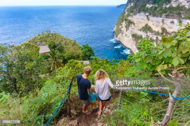Parents walking down coastal cliff with baby son, Bali, Indonesia