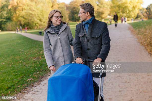 Parents walking in park with stroller