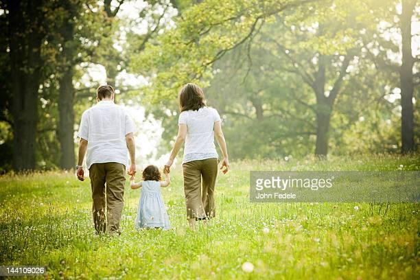 eltern und tochter zu fuß in feld - familie mit einem kind stock-fotos und bilder