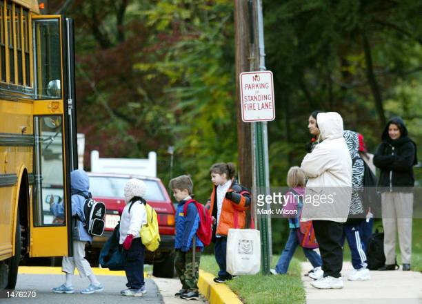 Parents watch as children step onto a Fairfax County school bus October 15 at Police headquarters in Falls Church, Virginia. Manger confirmed that...