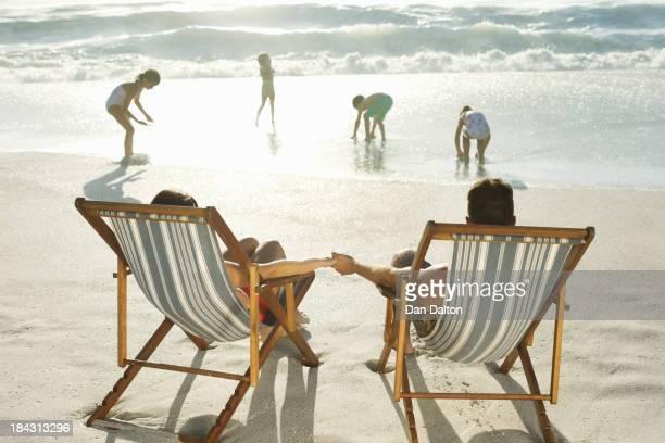 Eltern beobachten Kinder spielen am Strand