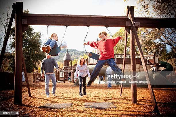 parents watching children swinging - mom flirting 個照片及圖片檔
