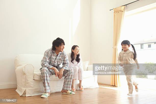 Parents Watching Daughter Running in Living Room
