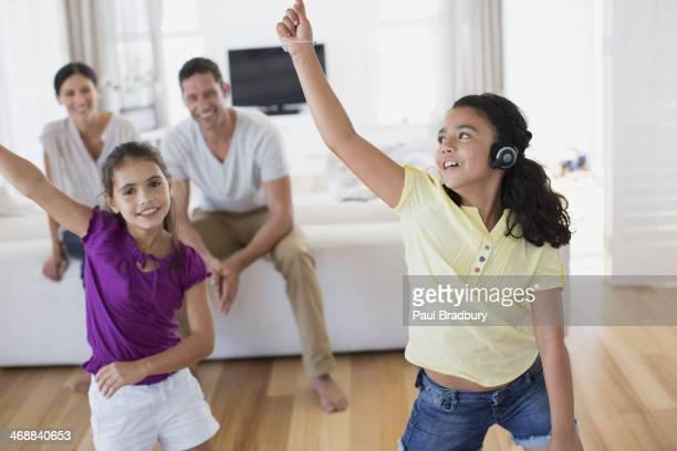 Parents watching daughters dance in living room
