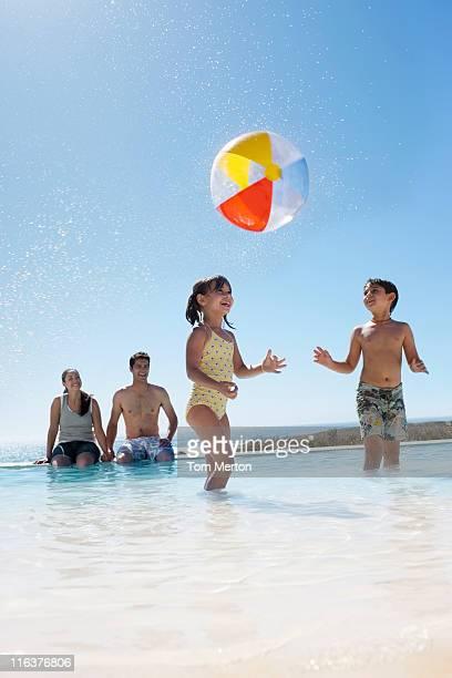 Parents en regardant les enfants jouer avec le ballon dans la piscine