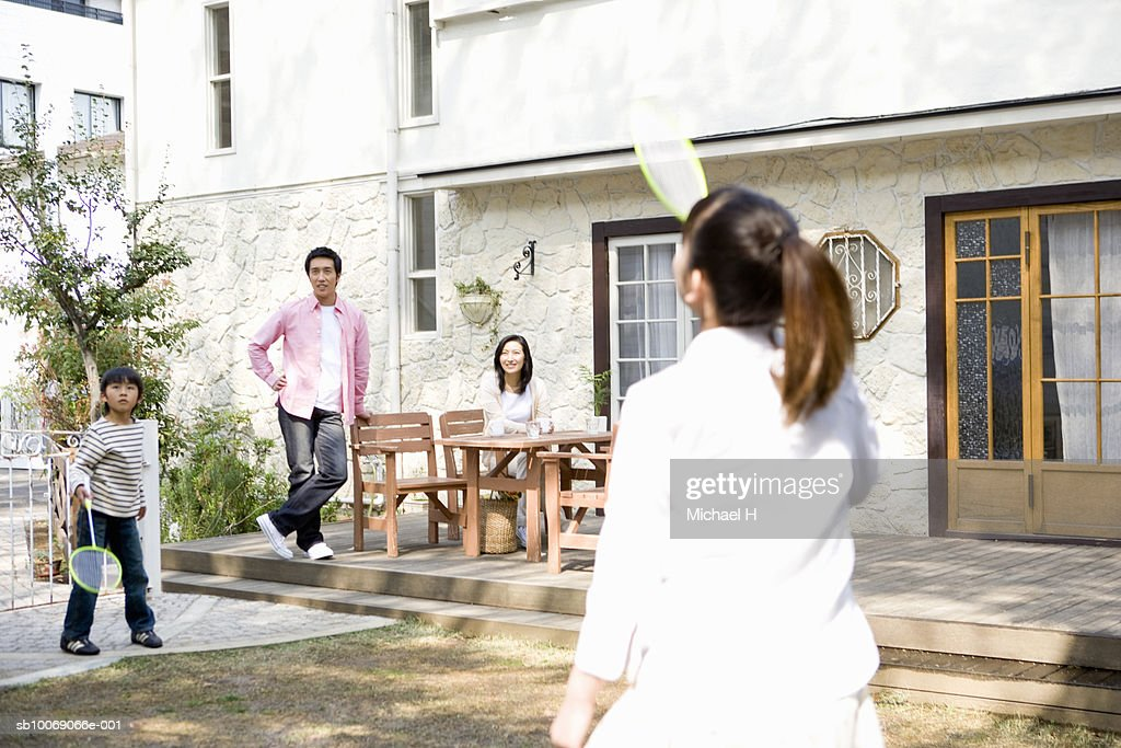 Parents watching son and daughter (6-13) play badminton outside house : Stockfoto