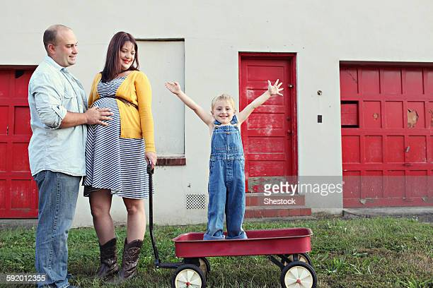 Parents watching son cheering in toy wagon