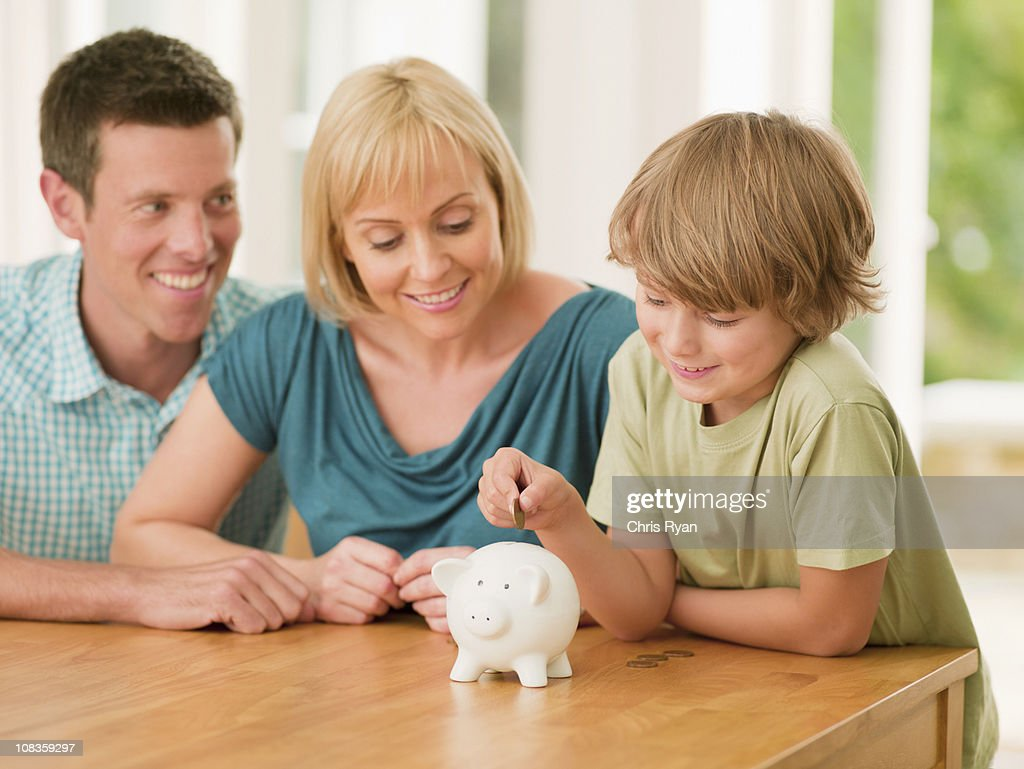 Parents watching son putting coin into piggy bank : Stock Photo