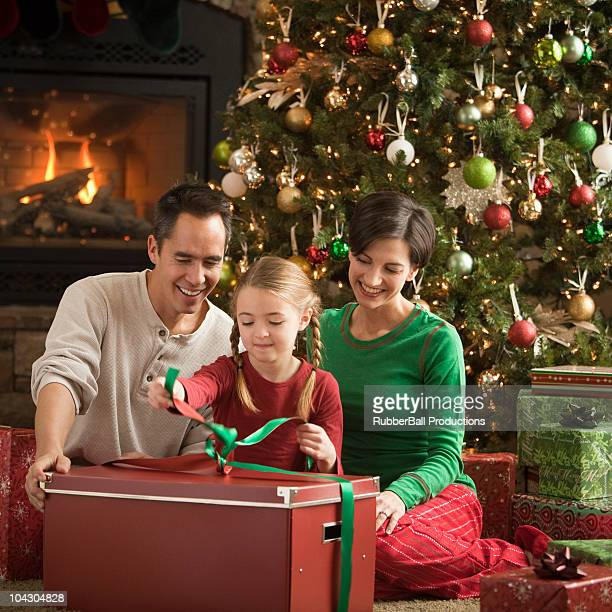 parents watching their daughter open a christmas present - orem utah stock pictures, royalty-free photos & images