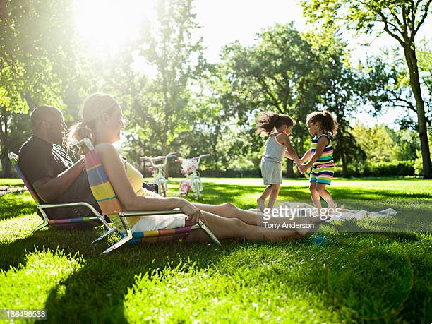 Parents watching twin daughters play in park
