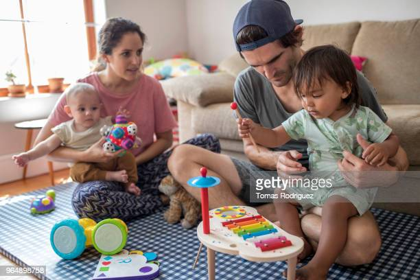 Parents with baby and toddler on their laps playing together