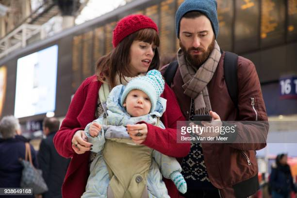 Parents with baby are checking mobile phone while walking through railway station.