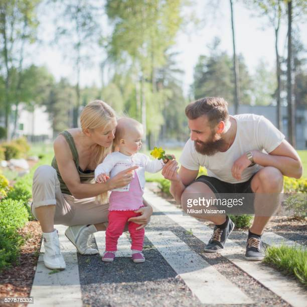 parents with baby girl (12-23 months) in garden - 12 23 months stock pictures, royalty-free photos & images