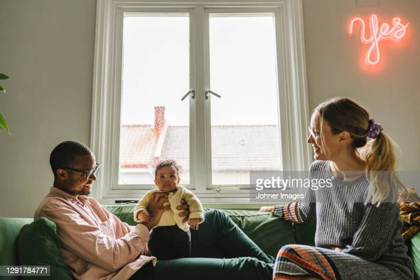 parents with baby girl sitting on sofa - paternity leave stock pictures, royalty-free photos & images