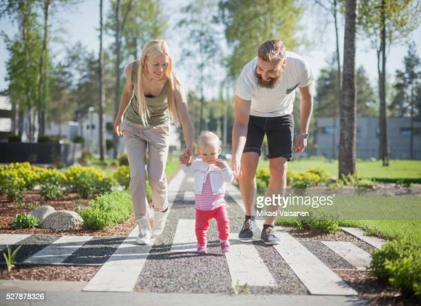 parents with baby girl (12-23 months) walking in garden - 12 23 months stock pictures, royalty-free photos & images