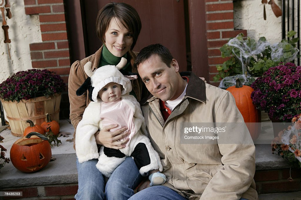 Parents with baby in cow costume : Stockfoto