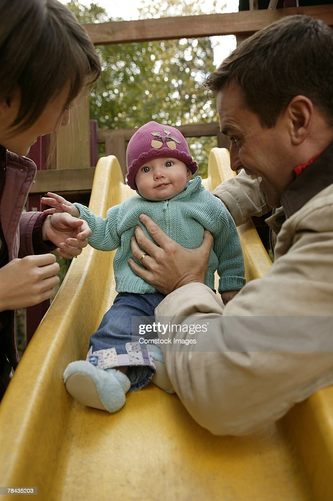 Parents with baby playing on slide : Stockfoto