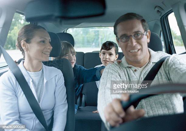 Parents with boy and girl in car wearing seatbelts, interior view