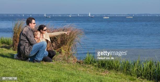 Eltern mit jungen Kind am See beobachten Segelboote auf dem Wasser