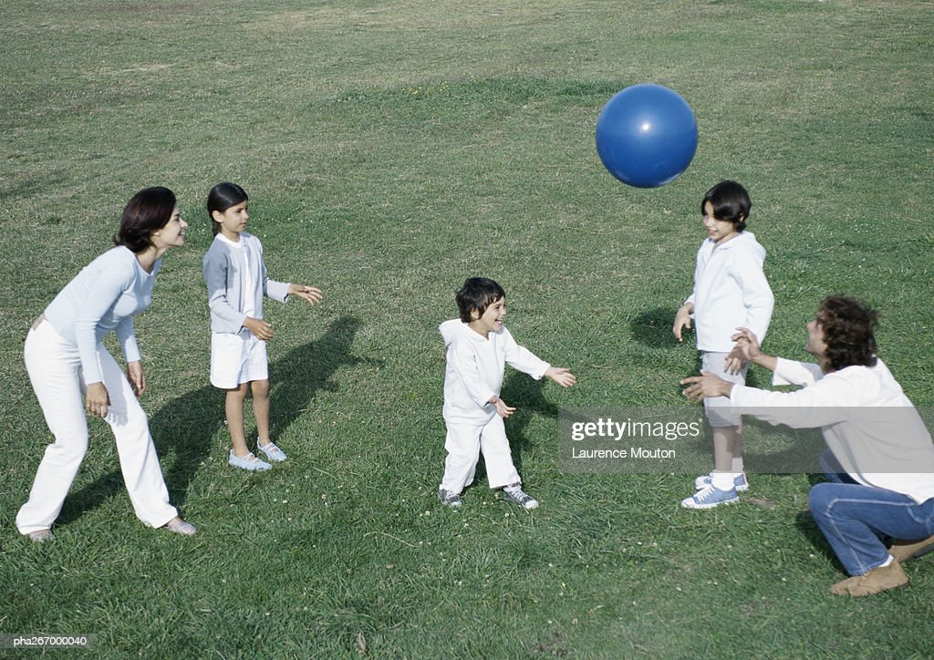 Parents with boys and girl playing ball on grass, full length : Stockfoto