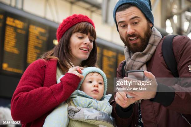 Parents with child are looking at mobile phone in railway station.