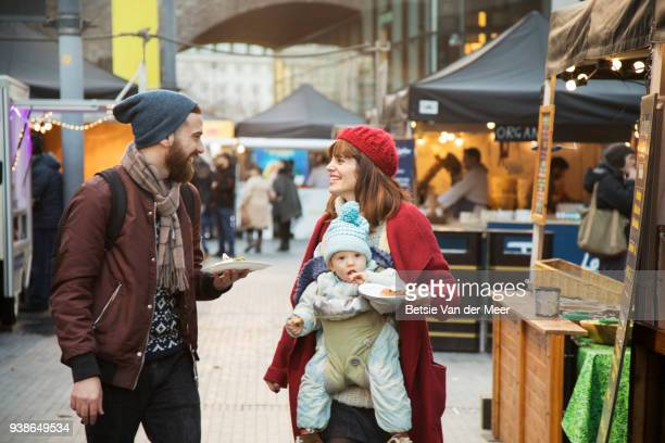 Parents with child are walking with take away food in street market
