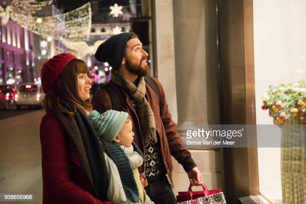 Parents with child look at shopwindow in city street.