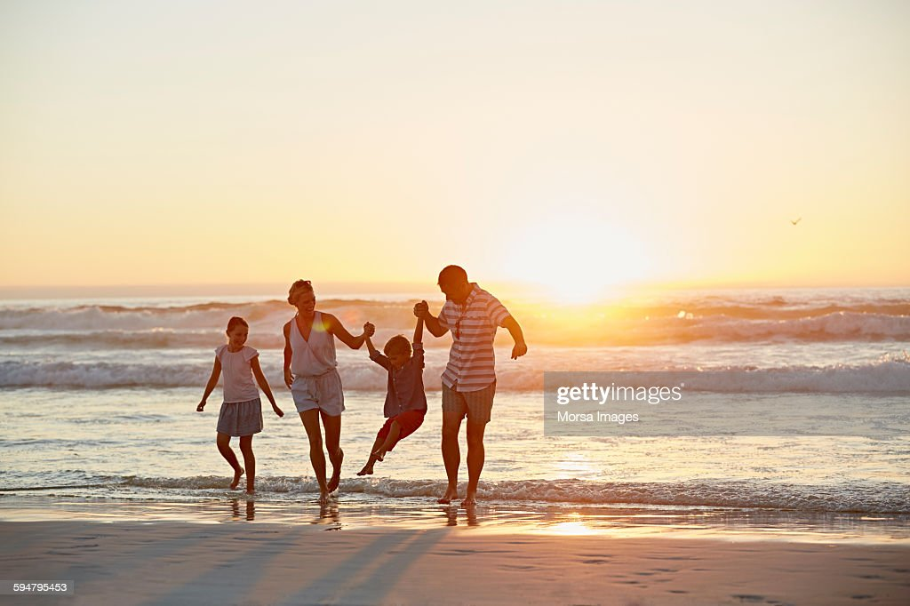 Parents with children enjoying vacation on beach : Foto stock